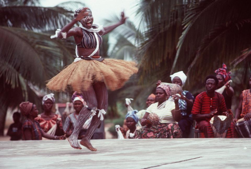 An African woman, wearing native garments, performs