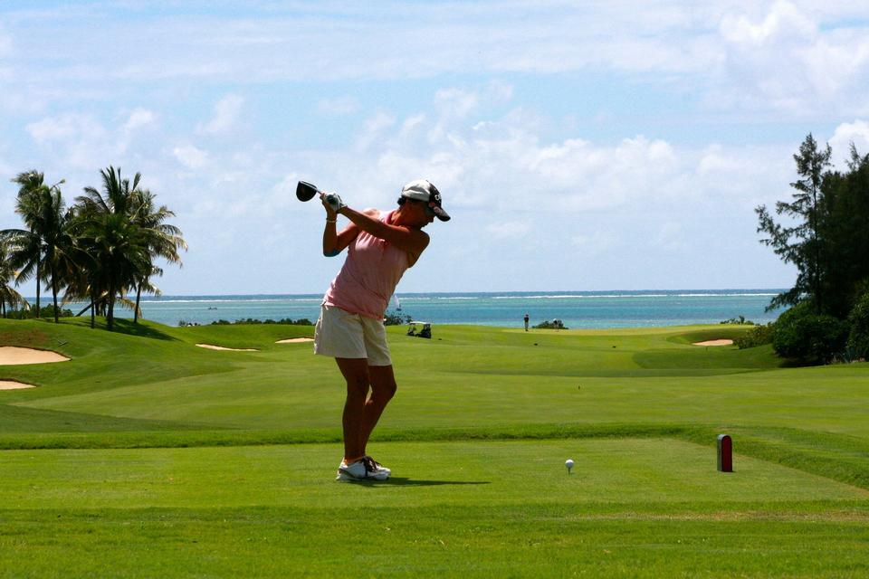 Girl golf player with driver teeing-off from tee-box to shoot