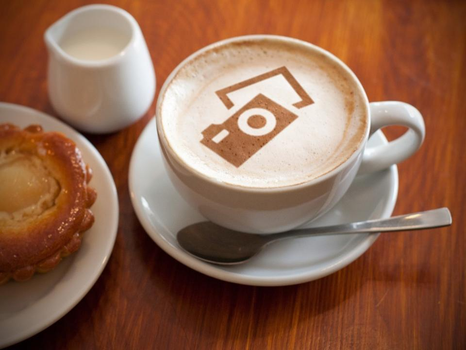 hot milk art coffee on wooden table Photo in old image style.